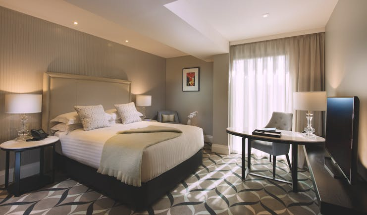 Superior queen room with large double bed, curtains, lamps and carpet