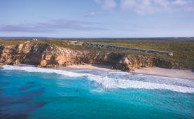 Exterior shot of Southern Ocean Lodge, long builifing nestled into cliff overlooking the sea