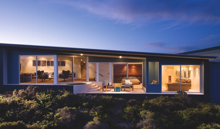 Exterior shot of the remarkable suite in Southern Ocean Lodge, long glass windows in bedroom, lounge and bathroom, private terrace with armchairs