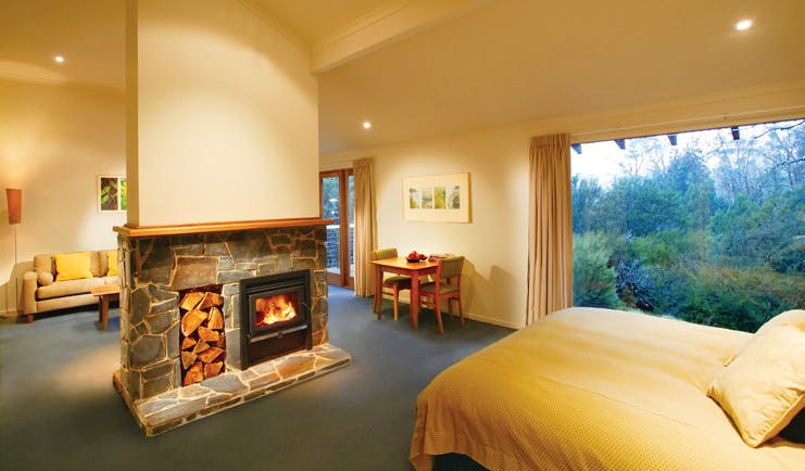 Cradle Mountain Lodge Tasmania bedroom view  fireplace sitting area and forest view
