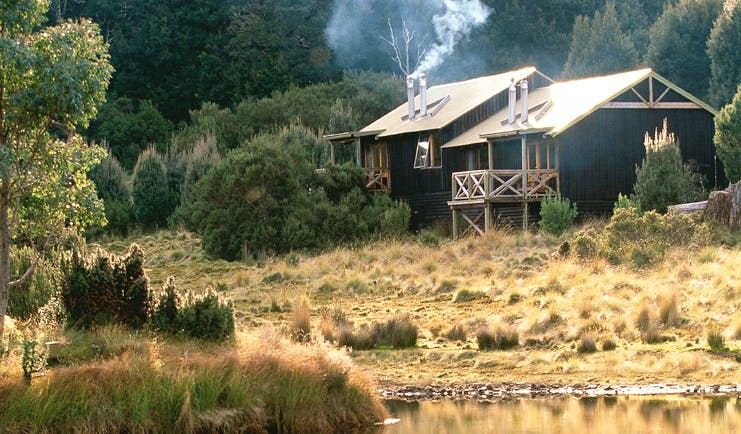 Cradle Mountain Lodge Tasmania exterior wood cabin surrounded by trees near water