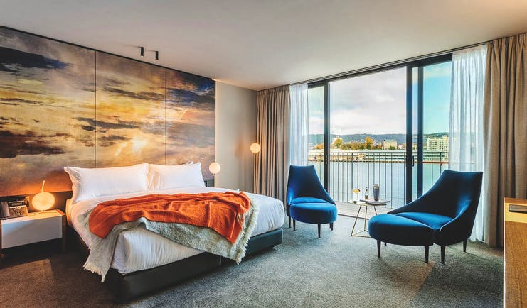 MACq01 guestroom, double bed, armchairs, modern decor with large painted sky mural wall, access to balcony overlooking marina