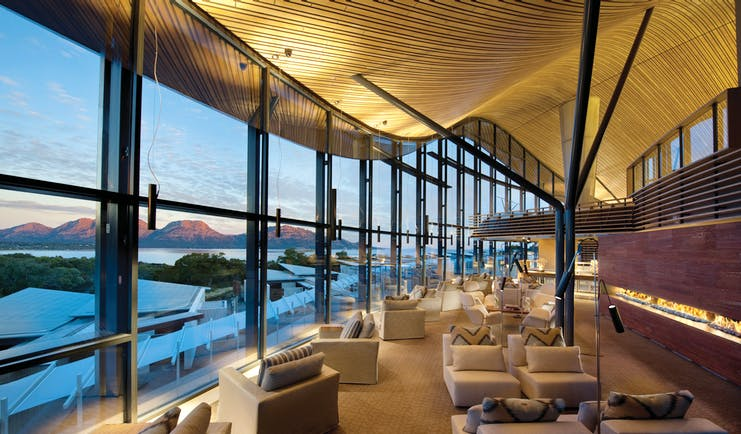 Saffire Freycinet Tasmania lounge with floor to ceiling windows overlooking mountains and sea