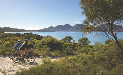 Saffire Freycinet Tasmania nature cycling two people cycling on dirt track with view of mountain and sea