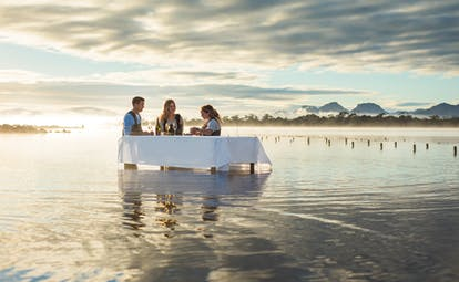 Saffire Freycinet Tasmania outdoor dining people at a table in the water at sunset shucking oysters