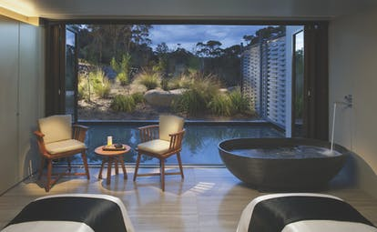 Saffire Freycinet Tasmania spa area with a freestanding bath and patio doors to outdoor pool
