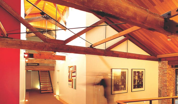 The Henry Jones Art Hotel Tasmania corridor with exposed beams and stonework and artwork on the walls