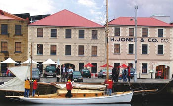 The Henry Jones Art Hotel Tasmania exterior large cream building overlooking a boat in a marina
