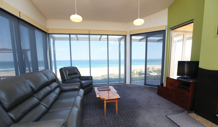 Chocolate Gannets Victoria and Melbourne lounge with large sofa floor to ceiling windows and beach view