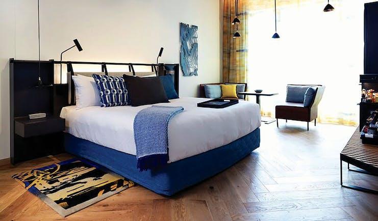 QT Melbourne executive room, bed, armchair, minimalist modern decor