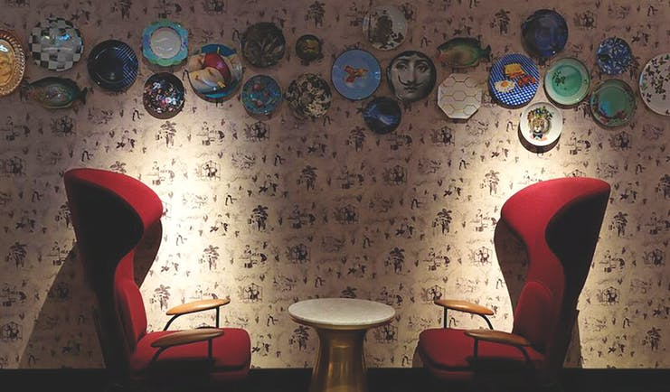 QT Melbourne Pascale bar, highbarked armchairs in red velvet, plates decorating wall
