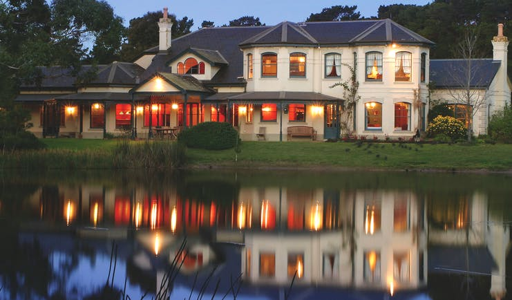Woodman Estate Victoria exterior large white building with grey roof and large windows overlooking a lake