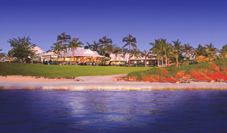 Cable Beach Club exterior shot from sea, hotel buildings, green lawns, palm trees, sand, sea