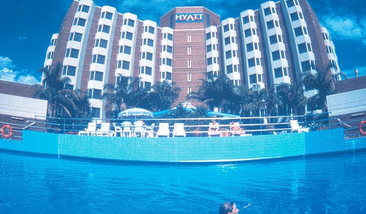 Exterior of hotel and swimming pool with building saying