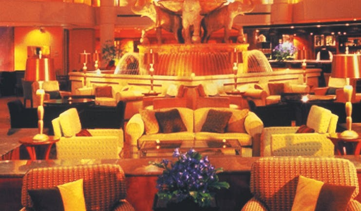 Lobby with high ceilings, arm chairs and orange lighting