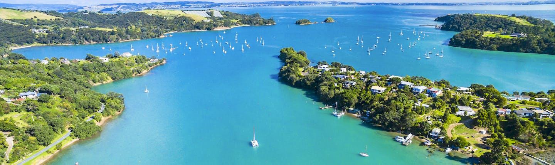 Putaki Bay in Waiheke Island near Auckland, bright blue ocean, boats on water, coastline