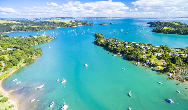 Putaki Bay in Waiheke Island near Auckland, bright blue ocean, boats on water, coastline