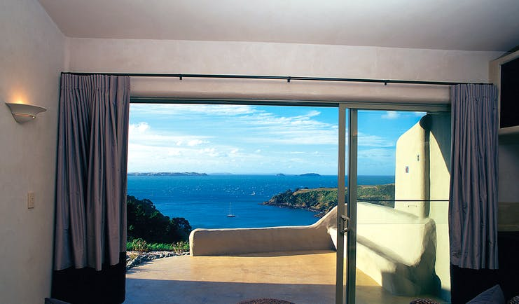 Guest room with bi-folding doors opening onto a patio looking out over the sea