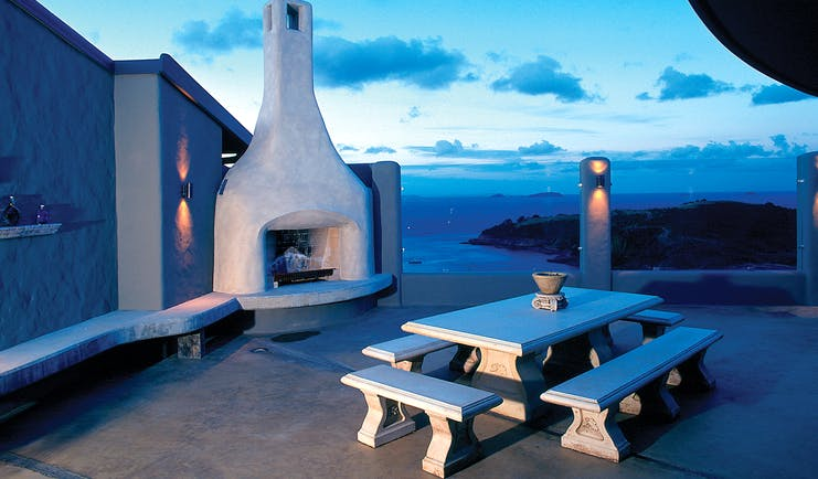 Outdoor terrace fireplace area with bench, fireplace and view over the sea