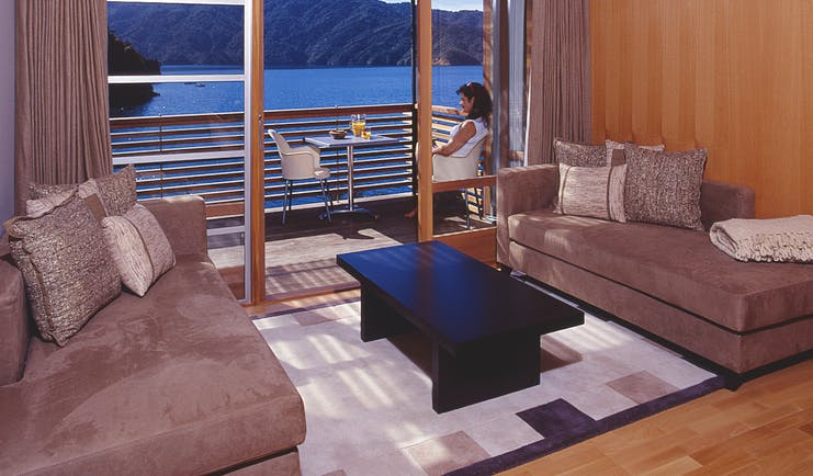 Bay of Many Coves Marlborough and Blenheim lounge area and woman sitting on a balcony with water and mountain view