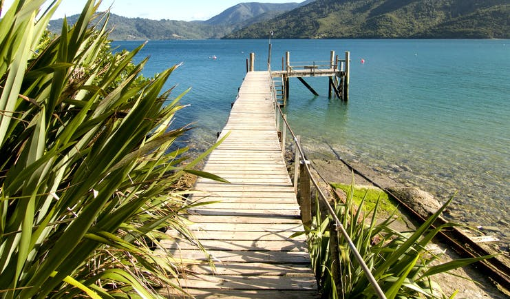 A view from the Queen Charlotte track in the Marlborough Sounds, wooden jetty, mountains, sea