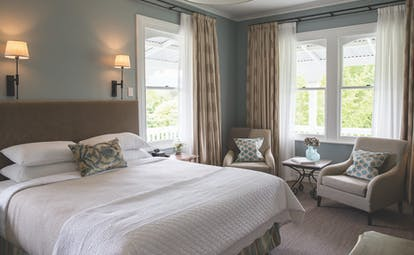 Marlborough Lodge Blenheim and Marlborough premium suite bedroom with two armchairs and porch view
