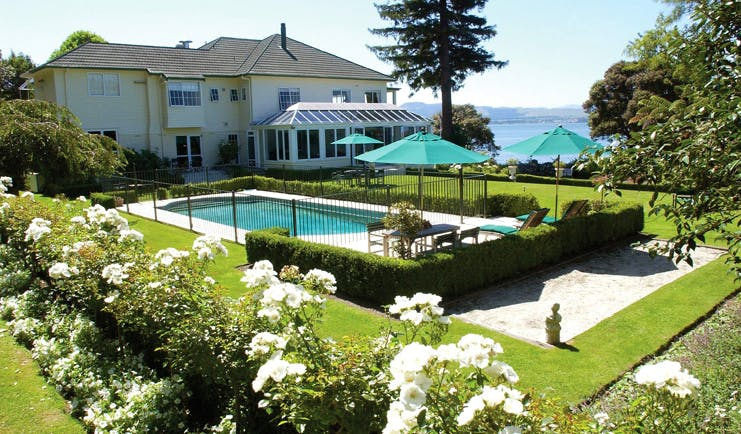 Black Swan Boutique Hotel Central North Island exterior white building overlooking outdoor swimming pool and garden