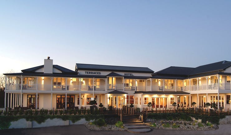 Exterior view of Hilton Lake Taupo with white building, dark tiled roof and lights inside lighting the yellow up with a yellow glow