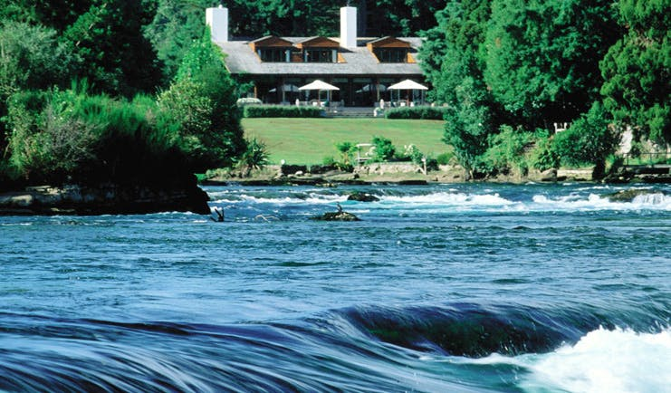 Huka Lodge Central North Island exterior view over river rapids to lodge and gardens