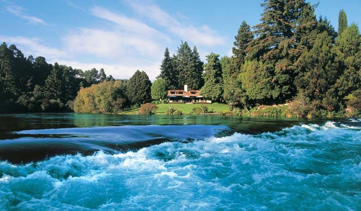 Huka Lodge Central North Island falls aerial view of a lodge and gardens surrounded by trees near river with rapids
