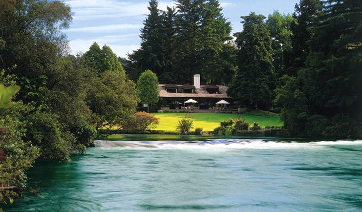 Huka Lodge Central North Island gardens view over river to lodge and gardens
