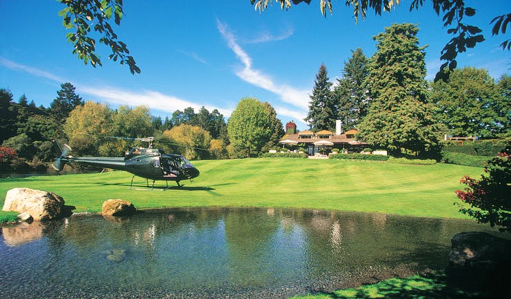 Huka Lodge Central North Island helicopter landing on a lawn near a lodge