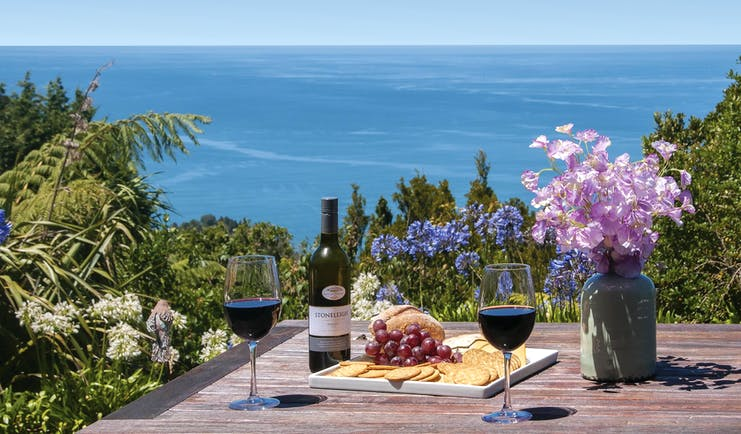 Poets Corner Lodge terrace, wine and cheese board on table, view overlooking the sea