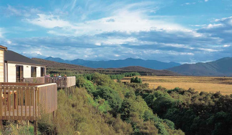 Poronui Ranch Central North Island countryside white lodges with balconies and view of mountains