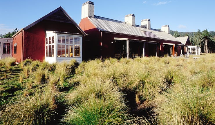 Poronui Ranch Central North Island exterior red lodge building with wild grass