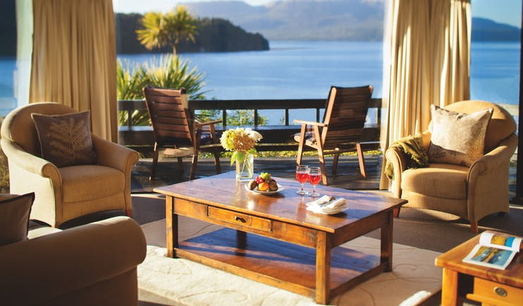 Solitaire Lodge suite, armchairs, coffee table, large windows with view over the sea