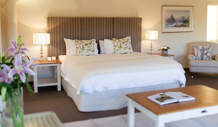 Solitaire Lodge Tarawera suite, double bed, armchairs, bright decor