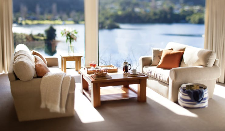 Solitaire Lodge villa suite living area, sofas table, large windows with views over the lakes