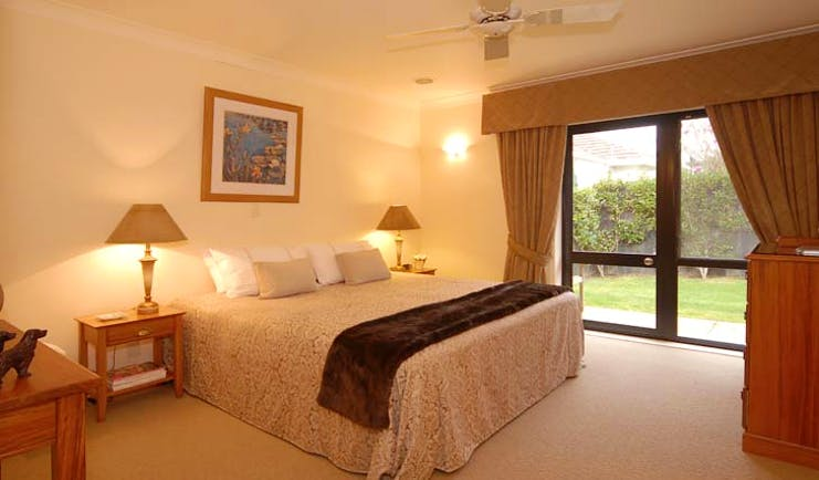 The Springs Central North Island Fairy Room bedroom with patio doors and garden view