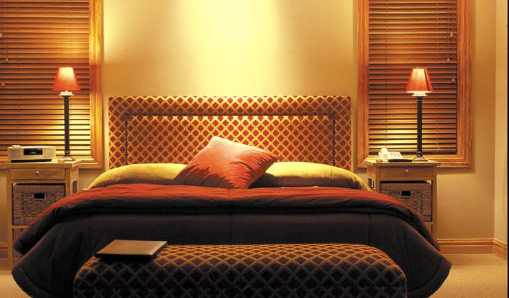 Treetops Lodge Central North Island bedroom with patterned head board and matching ottoman