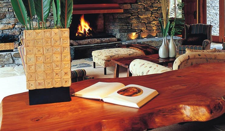 Treetops Lodge Central North Island fireplace lounge area with stone fireplace
