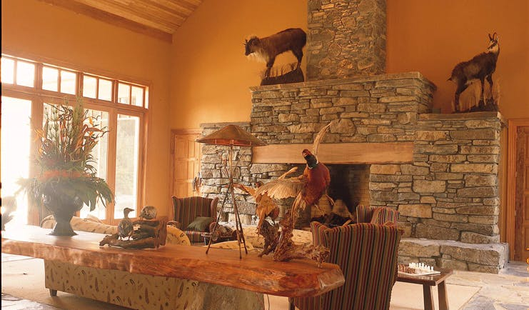 Treetops Lodge Central North Island lounge area with stone fireplace and taxidermy animals