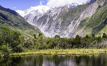 Mountain scene with lake and grey mountains in distance looking at Franz Josef glacier