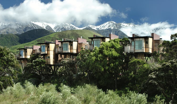 Hapuku Lodge Central South Island exterior wooden chalets on stilts among trees with mountain view