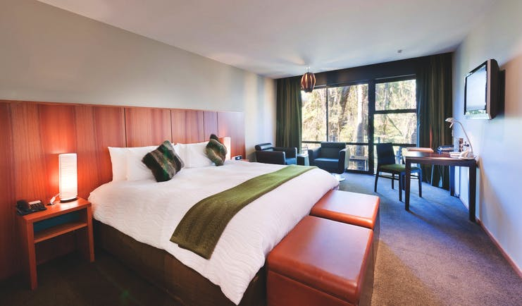 Te Waonui Forest Retreat Central South Island bedroom with seating area and large windows