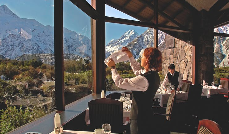 The Hermitage Hotel Central South Island restaurant woman cleaning wine glass in dining room with mountain views
