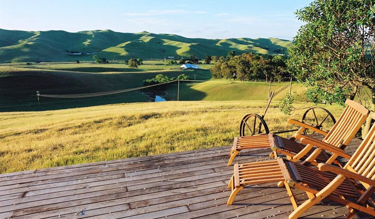 Greenhill Lodge Hawkes Lodge landscape deck two wooden loungers on a deck overlooking rolling green hills