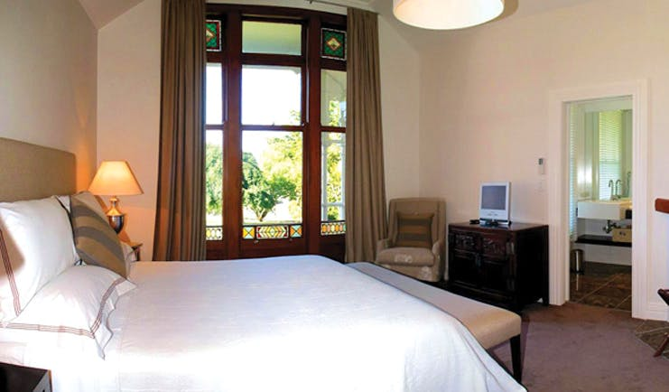 Greenhill Lodge Hawkes Lodge Mclean suite bedroom with large window and view to bathroom