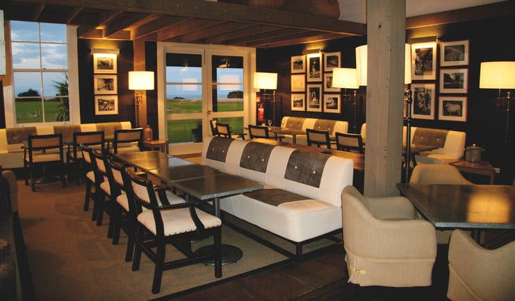 The Farm at Cape Kidnappers Hawkes Bay and Napier clubhouse lounge area with sofas tables with clifftop view