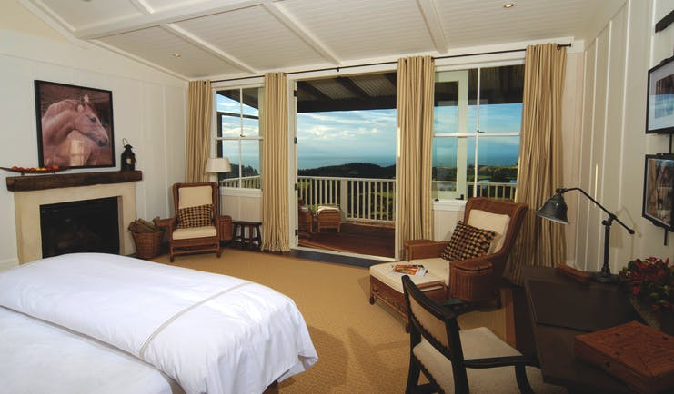 The Farm at Cape Kidnappers Hawkes Bay and Napier suite bedroom with two chairs and patio door to balcony